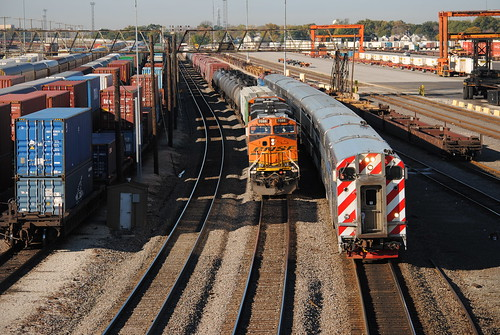 A Metra passes by at the BNSF Cicero Yard as a freight holds