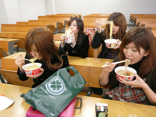Japan: Girls eating noodles in lecture theatre
