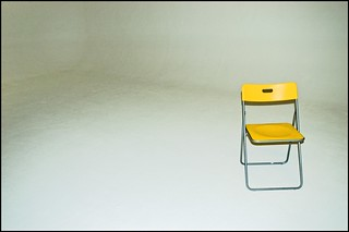 A Yellow Chair In A White Room