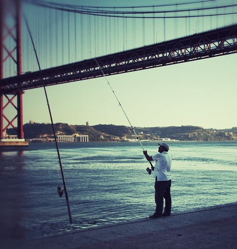 Fisherman in the shadow of the Ponte 25 Abril, Lisbon
