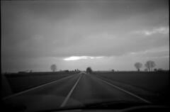 * (rumorebianco) Tags: bw film clouds 35mm driving toycamera streetphotography lomolca nocrop vignetting dramaticsky fromthecar lowfi roadtonowhere kodaktrix400 somewherebetweenmantovaandparma
