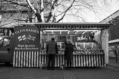The Butcher (Silver Machine) Tags: winchester hampshire streetphotography street candid butcher people couple dogs meat marketstall streetmarket blackwhite mono monochrome fujifilm fujifilmxt10 fujinonxf18mmf2r