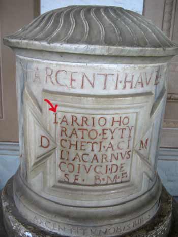 Ancient Italian marble column has missing letter chiseled in crooked.