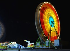 passing target (pbo31) Tags: california city longexposure carnival winter light motion black color wheel yellow night circle oakland march moving movement nikon ride spin fair spot revolution round spinning bayarea target bullseye ferriswheel rides d200 2008 funfair thrill lightstream abigfave