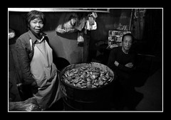 happily posing (fateless_gypsy) Tags: china people bw black smile night standing dark happy alley asia sitting oldman bin apron snack oldwoman 黄山 oldstreet huangshan anhui huizhou 安徽 blackwhitephotos 老街坊 燒餅 徽洲