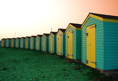 Row of huts (Andrea Kennard) Tags: door wood travel blue roof sea summer vacation england sky sun house holiday west green english beach home yellow fun outdoors sussex coast wooden seaside sand cabin warm paint view bright pastel room sandy small perspective culture sunny mini row structure storage pebble hut coastal chalet british shack colourful bathing seafront setting quaint viewpoint littlehampton informal