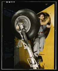 This woman worker at the Vultee-Nashville is shown making final adjustments in the wheel well of an inner wing before the installation of the landing gear, Nashville, Tenn. This [is] one of the numerous assembly operations in connection with the mass prod