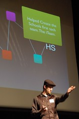 Article image: Chris Jones stands in front of a screen on stage during the 2011 MLTI Student Conference.