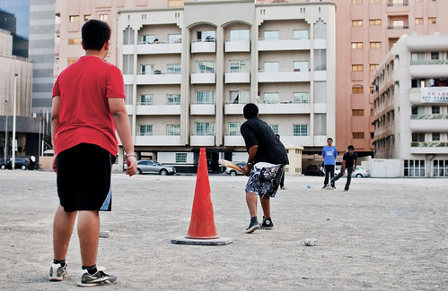 Teenagers playing cricket