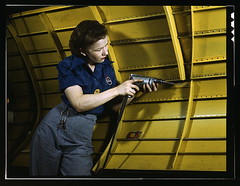 "Operating a hand drill at Vultee-Nashville, woman is working on a ""Vengeance"" dive bomber, Tennessee  (LOC) (The Library of Congress) Tags: woman color industry yellow plane vintage airplane keys women war keychain uniform nashville tennessee steel rosietheriveter aviation military rosie wwii dive slidefilm jeans worldwarii 1940s transparency ww2 4x5 lf libraryofcongress strength february bomber largeformat drill worldwar2 1943 assembly a31 wartime driller transparencies riveter fuselage vengeance manufacturing nashvilletn divebomber workforce vultee historicalphotographs february1943 colortransparency davidsoncounty wareffort xmlns:dc=httppurlorgdcelements11 dc:identifier=httphdllocgovlocpnpfsac1a35374 alfredtpalmer vulteeaircraftincorporated alfredpalmer divebomberassembly vengeancebomberassembly womandrilling vulteeaircraftcorporation vulteeaircraft vulteevengeance"