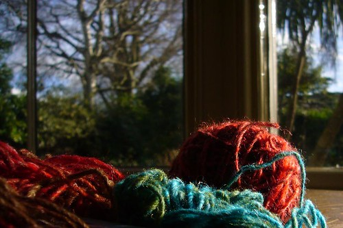 Kirsty Hall, photograph of balls of brightly coloured yarn in front of a blurred winter landscape
