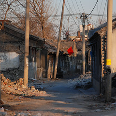 The sun sets on a hutong (NowJustNic) Tags: china street wire nikon destruction flag beijing cable chinesenewyear demolition newyear  hutong   telegraphpole chai lunarnewyear rubble   springfestival chunjie   500x500   xuanwu d80 yearoftherat nikkor18135mm caishikou  yearofthemouse