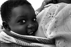 happy on mom's back (LindsayStark) Tags: africa travel portrait blackandwhite baby children war child mother conflict uganda humanrights humanitarian displaced idpcamp refugeecamp idps idp humanitarianaid emergencyrelief idpcamps postconflict waraffected conflictaffected platinumphoto