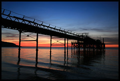 Totland Pier Sundown (s0ulsurfing) Tags: ocean blue winter light sunset shadow sea sky cloud sun sunlight holiday seascape black tourism beach water beautiful lines weather silhouette clouds composition wow reflections island evening bay coast pier interesting twilight holidays skies colours sundown bright dusk patterns sightseeing wide perspective shoreline silhouettes peaceful wideangle tourist calm explore coastal shore vectis isleofwight getty coastline ripples 2008 isle sights wight attraction 10mm totland eow sigma1020 sooc totlandbay s0ulsurfing visitorattraction anawesomeshot aplusphoto totlandpier isleofwightattractions isleofwightattraction welcomeuk