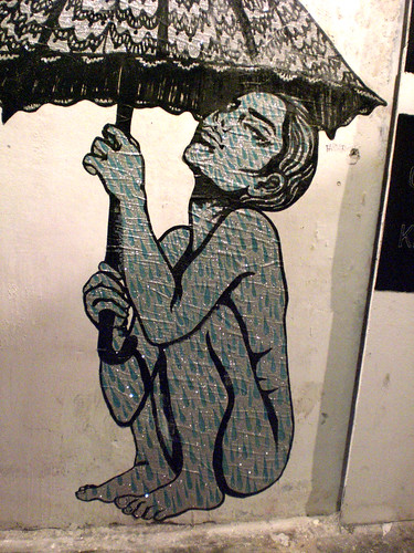 street art of a nude woman, folded into a tight crouch, looking up and holding an umbrella above her
