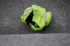 impressionist (Purricity) Tags: yellow ball hearts concrete war cement dirt torn around tennisball beckoning bounced brightyellow wetness trashbit