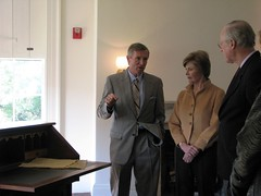 Director Frank Milligan, First lady Laura Bush, and National Trust President Richard Moe stand next to a reproduction of the desk that was in the Cottage when the Lincolns lived there. The original desk is at the White House.