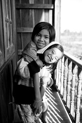 "Nuht & Nunn, sisters - Issan, Thailand (Sailing ""Footprints: Real to Reel"" (Ronn ashore)) Tags: girls light portrait blackandwhite kids sisters thailand happy asia village faces balcony smiles issan onexplore canoneos5d 10faves iloveyoursmile endhospitaldec2007"