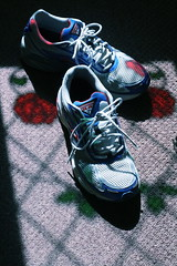 A slightly battered pair of running shoes beneath a stained-glass window