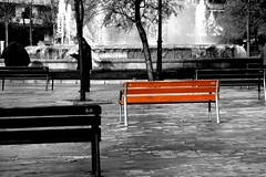 black and white photo of three park benches diagonally from foreground to background; the one in the middle is in color