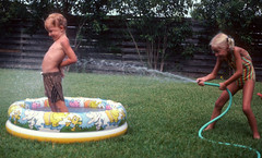 Backyard Water Park 1982--Yakima, Washington (Q of U) Tags: summer kids sisters backyard brothers siblings hose barefoot suntan pigtails swimsuit oldpicture yakima ordinarydays inflatablepool imgonnagetyou