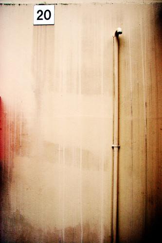 No answers here, move along. (Un mur sur lequel passe une gouttière et en haut duquel est inscrit le numéro 20 .. minimaliste)