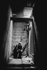 Alley Portrait (Ever & Anon Studios (www.andrewiwersen.com)) Tags: above light portrait blackandwhite man brick night trash dark concrete alley sitting young thinking lowkey seated