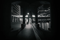 The Underbelly (TheFella) Tags: street uk longexposure greatbritain light shadow england blackandwhite bw canada slr london lamp monochrome night digital photoshop canon square person photography eos photo high europe moody dynamic unitedkingdom capital streetphotography atmosphere cranes nighttime photograph figure processing slowshutter gb docklands underneath dslr canarywharf range dlr hdr highdynamicrange enclosed shadowy docklandslightrailway postprocessing 500d heronquays photomatix