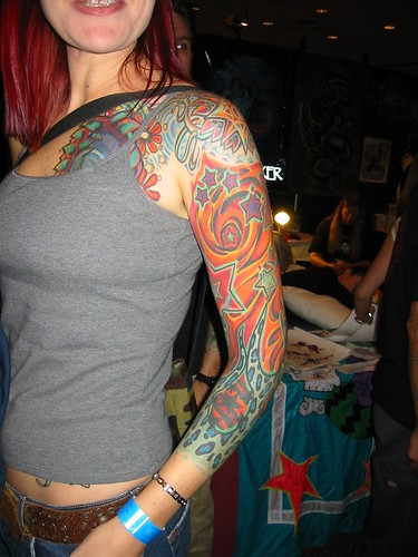 A vibrantly coloured sleeve tattoo on the left arm and shoulder of a female.