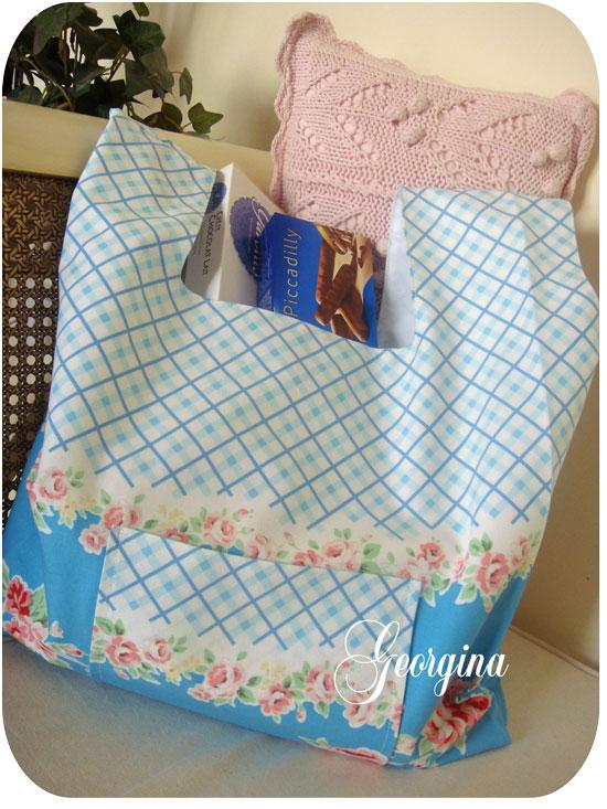 Bolsa de tela en tonos azules colocada sobre un sofá.