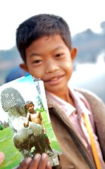 The Worst Postcard Ever (Joshua Liberman - The Tao of Photography) Tags: travel boy portrait kids digital canon children saturated funny cambodia cambodian village child bokeh candid buddhist watching innocent young streetphotography buddhism angkorwat postcards 5d spirituality charming selling playful quirky villager villagelife 70200mmf28l inquisative jerikojosh smallmonk childrenofangkorwat