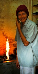 Oil is lit, cook at the Toast Bakery on his cell, Boudha, Kathmandu, Nepal