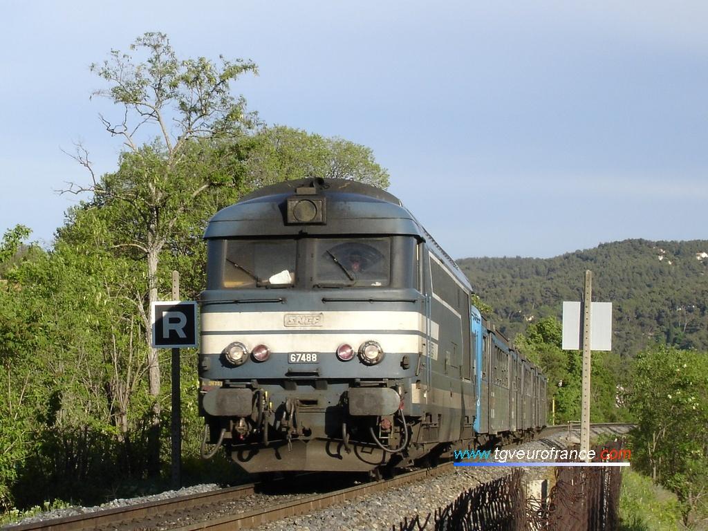 Une locomotive thermique BB 67400 en livrée Arzens approche de la gare d'Aix-en-Provence avec sa rame réversible régionale