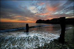 Broken stones - A November evening at Freshwater Bay, Isle of Wight (s0ulsurfing) Tags: ocean november blue light sunset shadow sea sky cliff cloud sun sunlight seascape color colour beach nature water weather silhouette rock clouds island evening bay coast lyrics twilight sand bravo rocks skies colours sundown natural bright dusk stones patterns wide shoreline silhouettes wideangle pebbles cliffs wash coastal shore foam vectis isleofwight coastline isle groyne backwash wight 2007 freshwater undertow 10mm paulweller freshwaterbay sigma1020 supershot s0ulsurfing thecloudappreciationsociety coastuk