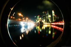 An alternative look at the singapore skyline (Silvr) Tags: new city bridge decorations water skyline night buildings reflections river festive lights singapore long exposure glow year chinese cny cbd wealth hongbao film:camera=lomofisheye2