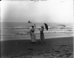 Rustico Beach, PE, 1916 (?) (Muse McCord Museum) Tags: ocean canada beach water sailboat umbrella boat sand women waves dress horizon sails hats footprints skirt dresses farewell princeedwardisland goodbye waving 20thcentury auf pei 1916 adeus wiedersehen mccordmuseum notman musemccord rusticobeach commons:event=commonground2009