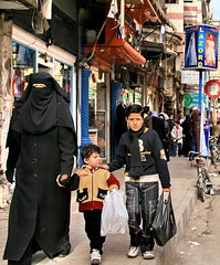 Family Shopping (hazy jenius) Tags: world street city trip travel family people urban woman kids shopping veil market muslim islam headscarf hijab strangers photojournalism backpack saudi cannon bazaar niqab souq global euphrates deirezzur hejab deirezzor alfurat dayrazzaur