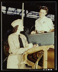 "Formerly a sociology major at the University of Southern California, Mrs. Eloise J. Ellis (right) now ""keeps 'em flyin'"" at the Naval Air Base, Corpus Christi, Texas. She is a supervisor under civil service in the Assembly and Repair Department. It is her"
