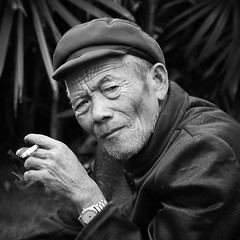 The Face Of China V - Earning Another Wrinkle (Michael Steverson) Tags: china old portrait bw man hat leather beard nikon asia cigarette watch chinese games smoking explore study jacket elderly chinadigitaltimes nikkor retired wrinkles allrightsreserved guangxi expatriate liuzhou d40 expatriategames