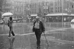 No umbrella (Heywood Industries) Tags: street blackandwhite bw wet pavement steps sydney australia oldman ishootfilm sidewalk ilfordhp5 walkingstick 400 newsouthwales intersection rodinal raining footpath georgestreet olympusom1 queenvictoriabuilding parkstreet testroll noumbrella heywoodindustries