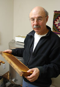 Allen Garr with a frame of waxen honeycombs used inside his bee boxes.