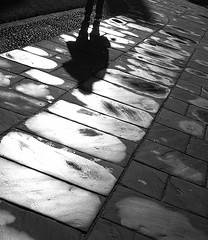 Departure (robep) Tags: uk cambridge shadow england bw sun wet rain stone person university glare path walk paving kingscollege
