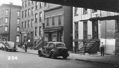 Dreary daily street life at 617 Jersey Avenue with the 6th Street Erie Railroad running overhead blocking out much of the sunlight. An old beat up car from the early 1930s with no front hub caps is parked. Jersey City. May 1950 (wavz13) Tags: oldphotographs oldphotos 1950sphotographs 1950sphotos oldphotography 1950sphotography vintagephotographs vintagephotos vintagephotography filmphotos filmphotography historicphotographs historicphotos historicphotography railroadphotos railroadphotography railroads oldbuildings vintagebuildings 19thcentury oldconstruction vintageconstruction oldhouse oldhouses vintagehouse vintagehouses depressing bleak noir noire dark jerseycityphotographs jerseycityphotos oldjerseycityphotography oldjerseycityphotos oldjerseycity vintagejerseycity vintagejerseycityphotography urbanphotography urbanphotos urbanscenes cityphotography cityphotos cityscenes rustycars beatercars vintagecars vintagecar oldcar oldcars 1940scars 1950scars collectiblecars collectablecars antiquecars urbanstreets streetphotography jerseycityhistory newjerseyphotographs newjerseyphotos oldnewjersey vintagenewjersey newjerseyhistory 1930scars urban junkcars gritty