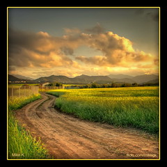 Winding dirt road (Mike G. K.) Tags: road light sunset mountains green nature grass yellow clouds canon square landscape glow view earth path cyprus explore fields fp frontpage hdr blueribbonwinner photomatix explored earthroad 3exp sandroad klirou  yourwonderland malounta malounda   aredhiou arediou clirou clerou mikegk:gettyimages=submitted