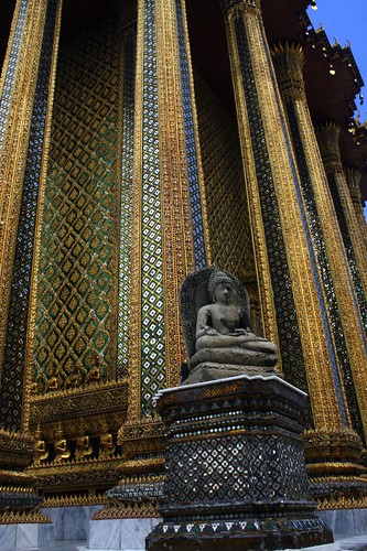 A buddha sits serenely in front of a spectacular mosaic building