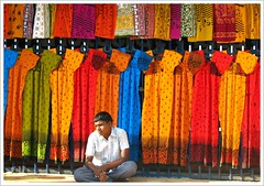 | Tired Boy & Bright Colors | (Rajendran Rajesh) Tags: blue boy red india colors shop dress selling pondicherry nightdress roadsideshop dullboy abigfave rajeshpics canons5is colourartaward