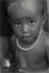Little girl with necklace-Phnom Penh (kinginexile) Tags: life portrait baby girl kids portraits children eyes asia cambodia phnompenh 2007 perplexity itsongmirrorssoutheastasia