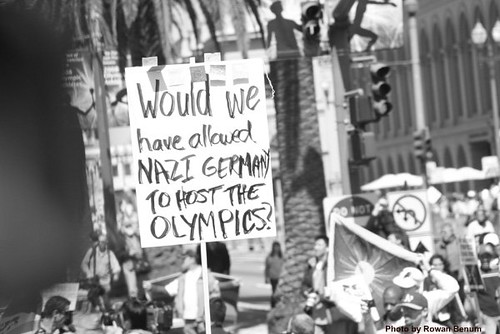 Protester with sign:  Would we have allowed Nazi Germany to host the Olympics?