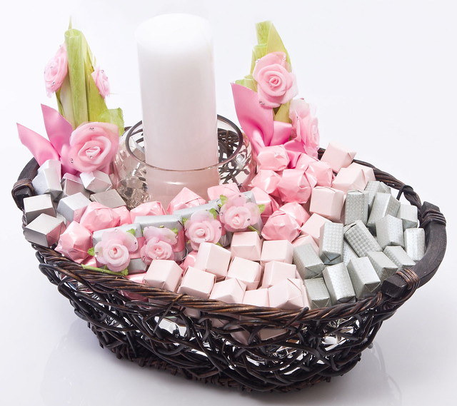 Rustic wooden basket decorated with a white candle and silk flowers