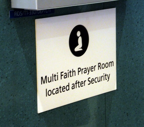 A sign indicating an available multifaith prayer room at an airport.